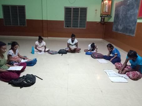 Mädchen lernen auf dem Boden in Anugraha